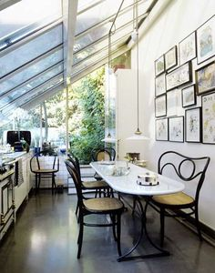 This light and airy kitchen was designed by acclaimed French designer and interior architect Andree Putman. We love the slanted glass roof and the feeling of being so close to the outdoors. And who wouldn't love those vintage French cane chairs? See another photo below:
