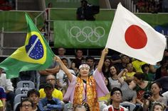 US women hold off scrappy Netherlands team in 5 sets  -  August 8, 2016  -        A fan waves flags during a Women's preliminary volleyball match between Japan and Cameroon at the 2016 Summer Olympics in Rio de Janeiro, Brazil, Monday, Aug. 8, 2016. (AP Photo/Matt Rourke)