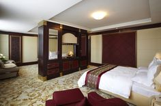 This is the opposing view of the same room, showcasing the bed with decorative red covering on white sheets.