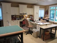 New studio for The Little Yellow Farmhouse.  Check out the details here: two complete work stations,covered storage, floor to ceiling cabinets, a big window, smooth sweepable floor.  one the wall you cannot see are floor to ceiling racks to store her fabric (she's a quilter), entrance to the family area, and a FIREPLACE!