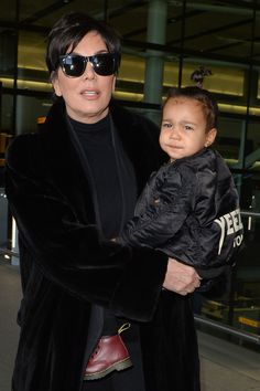 Kris Jenner carries North West at Heathrow airport in London on March 2, 2015.   - Cosmopolitan.com