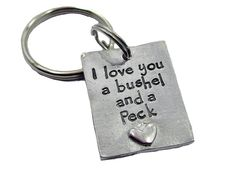 "This cute keychaine has a fine pewter rectangle and is hand stamped with ""I love you a bushel and a peck"""