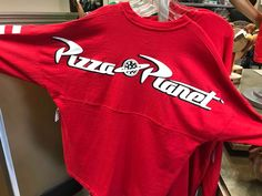 Get ready to blast off in style with the fun new Pizza Planet Spirit Jersey, now at Hollywood Studios! This bold jersey is inspired by the iconic restaurant fro Spirit Jersey, Cute Disney Outfits, Planet Logo, Fraternity Collection, Pizza Planet, Mad Hatter Hats, Disney Aesthetic, Disney Merchandise, Hollywood Studios