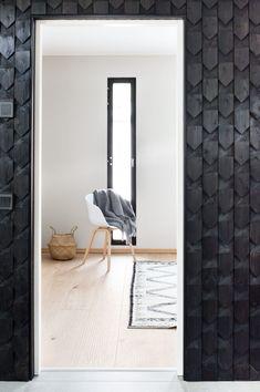 Musta kuvioitu puupaneeliseinä kehystää kauniisti ovea ja toivottaa eteisessä tervetulleeksi, Siparila.