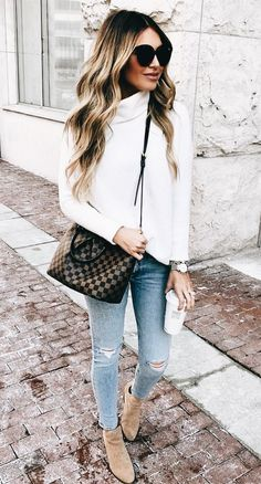 White cowl knit sweater with distressed denim jeans, cute handbag and booties.