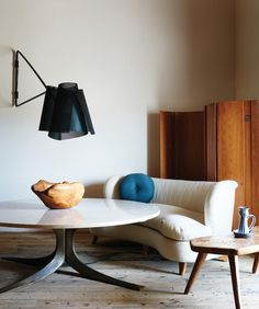 The farmhouse's living room, where a lamp by the designer spotlights a vintage travertine table...