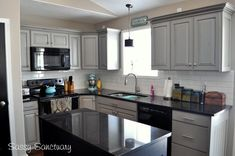 HOW TO make black appliances work in a kitchen with gray painted kitchen cabinets or white cabinets. Black granite countertop and subway tile shown #KitchenDesign #DecoratingIdeas