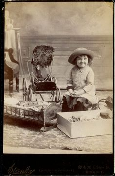 This little girl looks so happy, she should as all the lovely toys she has indicates she is from a family that think a great deal of her.  Although her dress is plain, the dolls and their bed are very nice.