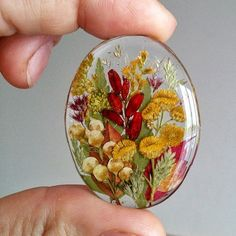 Resin cabochon filled with flowers and other botanicals. Could be made into a necklace by gluing on a bail or by creating a beaded bezel. Epoxy Resin Art, Uv Resin, Resin Artwork, Resin Charms, Resin Casting, Sewing Leather, Resin Flowers, Diy Home Crafts, Diy Earrings