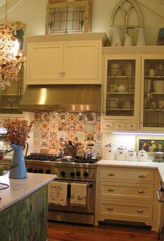 old reclaimed tiles for the cooktop back splash chandelier in the kitchen and the decorations top of cabinetsabove