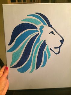 This is a hand painted Alpha Delta Pi canvas with Alphie on it. The background is light blue, and then there is a pattern of blue paint, teal