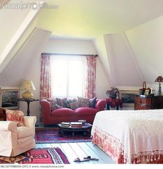 Couch besides a bed in an Attic bedroom