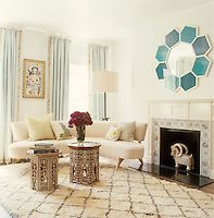 Cool tones of turquoise and white in a living room furnished  with a pair of inlaid Indian tables and a curved sofa upholstered in cream linen