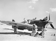 A Hawker Hurricane Mark IV of No. 6 Squadron RAF being serviced on an airfield in Italy, probably Foggia Main, prior to a sortie over the Adriatic, 24 July 1944. Note the asymmetric wing loading on the aircraft, consisting of a 44-gallon long-range fuel tank under the port wing, and four 3-inch rocket projectiles under the starboard: also the Type G45 gun camera being serviced by the airman standing second from the right.
