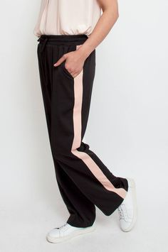 These wide-leg trousers are sure to become a staple for casual days. The black stretch material makes this pair extra comfortable for a laid-back look of luxe. It features nude athleticwear-inspired stripes on the sides, an elasticated waistband and side pockets. Wear yours with a blazer for sophisticated balance. By Neo Noir.      Available at Sienna & Lois.