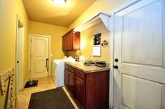 The utility room provides access to the two-car garage and is quite spacious with room for two front loaders, has plenty of storage space, a folding counter and hanging rack.