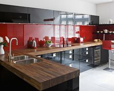 Despite the modern look of the black and red in this kitchen, you can see that wood can be used to pull things together.