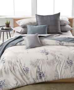 Transform your bedroom into a relaxing mountain retreat with the cool natural ground and smoke-colored tree print of this Alpine Meadow duvet cover from Calvin Klein. | Cotton | Machine washable | Imp
