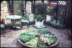 An Old Wagon Wheel - repurposed by planting each spoke with a different herb.....lovely!
