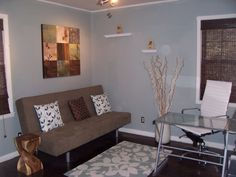 I like the blue walls, the floating shelves, the futon, and the rug.  Needs more black accents, less white.