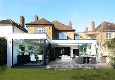 Contemporary single storey extension to a family home in London. They wanted to bring a sense of openess to their semi detached home. We did this by including an L shaped extension with a raised deck to create inside and outside living spaces. House Extension Plans, House Extension Design, Glass Extension, Rear Extension, House Design, Extension Ideas, L Shaped Kitchen Extension, 1930s House Extension, Extension Google