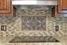 #Kitchen backsplash idea. Gray/taupe/green mosaic tile with bronze accent piece.