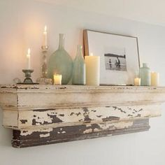 beautiful mantle decor - candles, picture & old blue bottles
