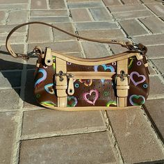 Xoxo purse Small brown xoxo purse with colored hearts. Blue silk lining inside. Zip pocket & 2 other small pockets inside.  Small stain shown in last picture otherwise excellent condition! XOXO Bags Mini Bags