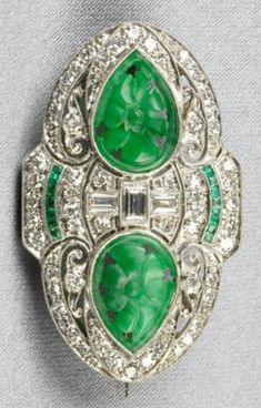 An Art Deco, Carved Jade, Emerald, and Diamond Brooch. Each set with two shaped jades carved with foliate motifs, baguette-, and single-cut diamond meleé accents, fancy-cut emerald highlights, millegrain accents, removable 14kt white gold pin stem, length 1 1/2 in. #ArtDeco #brooch