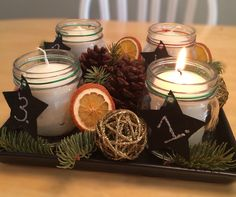 Variation of an Advent Wreath with pieces of pine, dried orange slices, pinecones, golden decorative balls, and candles in cute mason jars. Simple and so cute!