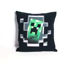 "One of a kind Minecraft pillow featuring a Creeper peeking through a hole in the wall. - As soft as your favorite tee shirt - 12"" x 12"" pillow - Envelope closure in the back for easy washing and care"