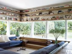 Shelves built above the cinema room's windows outline the perimeter of a sunken seating area | archdigest.com