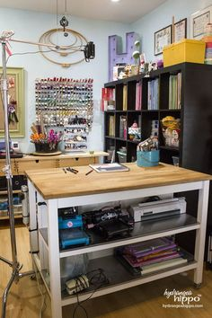 Keep larger tools on tables at the ready. Store tools you use less often on shelving, like the serger sewing machine on the bottom shelf of a work table in this photo