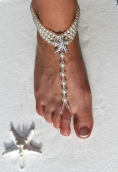 Unique barefoot sandals with a beach themed design made with a large sparkling rhinestone starfish and white colored lustrous pearl beads doubled wrapped around the ankle