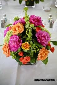 """The rehearsal dinner will feature centerpieces of 8"""" clear glass cylinder vases overflowing with fuchsia peonies, orange roses, purple freesia, orange spray roses, green hypericum berries, bells of Ireland, and lemon leaves with green ti leaves inside the vase hiding the stems."""