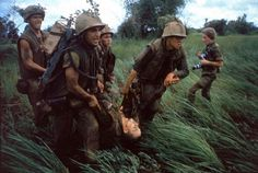 """<b>Caption from LIFE.</b> """"Four Marines recover the body of a fifth as their company comes under fire near Hill 484."""" Vietnam, October 1966. NOTE: At right is the French-born photojournalist Catherine Leroy (1945 - 2006); she was cropped out of the version of this photo that originally ran in LIFE."""
