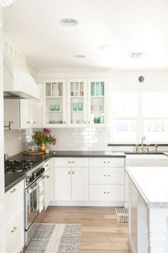 Eclectic Home Tour - Rafterhouse - Tour this stunning home with classic white kitchen, subway tile and glass cabinets - White Kitchen Cabinets, Kitchen Redo, Kitchen Tiles, New Kitchen, Glass Cabinets, Black Countertops White Cabinets, Shaker Cabinets, Kitchen Cabinetry, Kitchen Interior