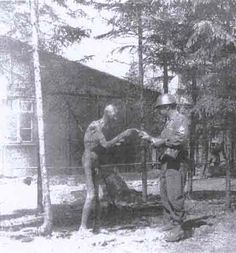 Ebensee After Liberation. Sgt. Lipman giving cigarette to liberated prisoner. (photographer unknown)
