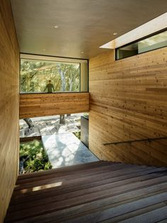 """The front of the house features concrete steps that connect to a large staircase. The stairs pass under a """"bridge"""" and ascend to the backyard"""