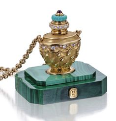 14 KARAT GOLD AND GEM-SET PERFUME BOTTLE PENDANT-NECKLACE AND MALACHITE BASE, HARRY WINSTON The textured gold perfume bottle set with round diamonds weighing approximately 1.40 carats, the top accented by turquoise cabochons and a cabochon ruby, suspended from a gold link chain, gross weight approximately 63 dwts., length 26 inches, together with a rectangular malachite base, signed HW for Harry Winston