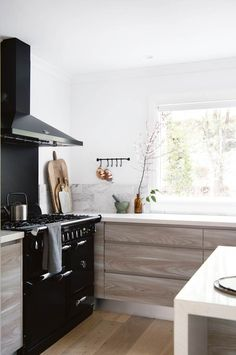 A modern country kitchen with sleek black wood-burning stove and timber veneer cabinetry Kitchen Stand, Home, Modern Country Kitchens, Kitchen Design, Country Kitchen, Oven Design, Flooring Trends, Alternative Flooring, Kitchen Themes