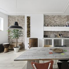 Netherlands-based firm Global Architects has transformed a traditional apartment on the top floor of a mansion in The Hague into a neutral-toned, open-plan space with a contemporary feel. In the kitchen, stainless-steel cabinetry creates an industrial vibe, while a table made from raw-grain wooden boards and panels of exposed brickwork on the walls add elements of rusticity.