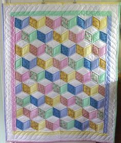 Amish made Tumbling Blocks baby quilt. A difficult to make and very old Amish quilt pattern. Created using unisex colors and a mix of solid and patterns. #Babyquiltpatterns