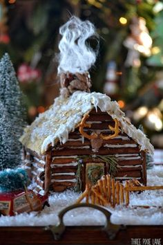 Gingerbread log cabin startin with a base of a purchased gingerbread house and she gives very detailed instructions Three Pixie Lane