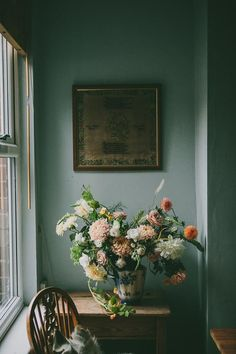 large drooping flowers against moody blue painted walls