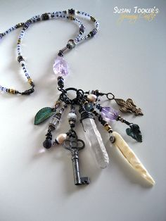 GARDEN ALCHEMY is an amulet necklace in the lariat style, made with Amethyst beads and Victorian charms. Created by Susan Tooker of Spinning Castle.