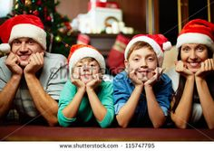 Portrait of friendly family in Santa caps looking at camera on Christmas evening - stock photo
