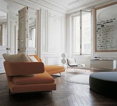 Richly detailed white walls and ceiling + orange contemporary statement sofa.