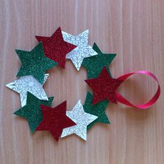 Punched star mini wreath, punched stars made from glitter cards and recycled Christmas cards ribbon on a cardboard wreath shape, and a ribbon loop stapled to it, hidden by a star.