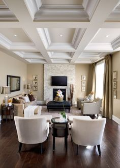 Benjamin Moore Greenbrier Beige is one of the best neutral paint colours with a subtle undertone. In living room with coffered ceilings and stone fireplace by Jane Lockhart